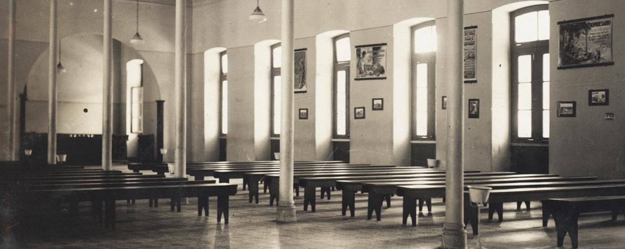A imagem mostra, em uma sala, bancos compridos dispostos em duas filas, com pilastras no meio