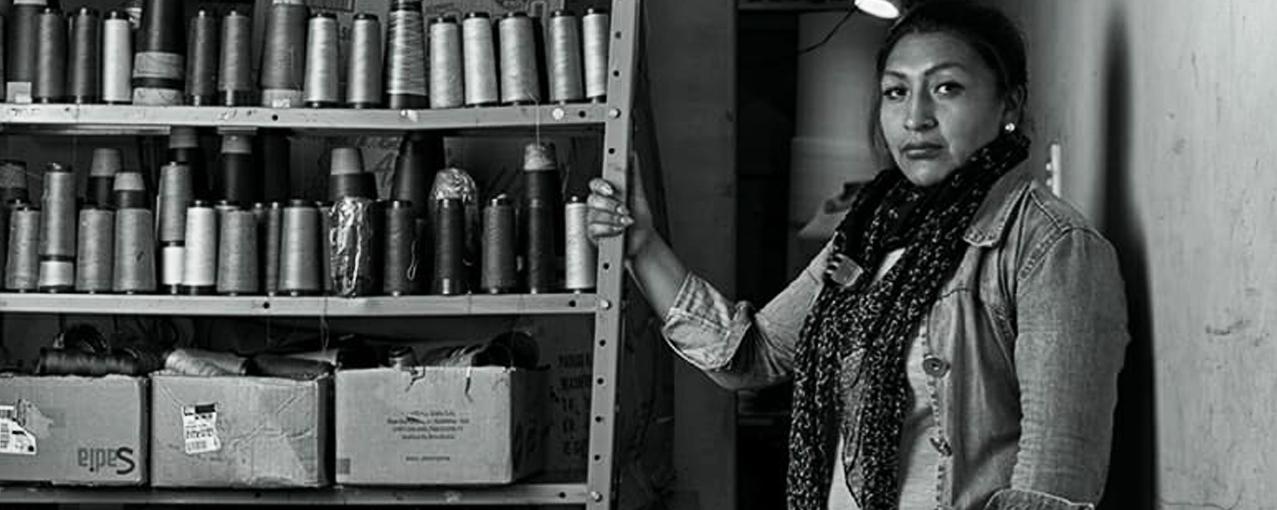 Mulher boliviana ao lado de uma prateleira com rolos de linha de costura