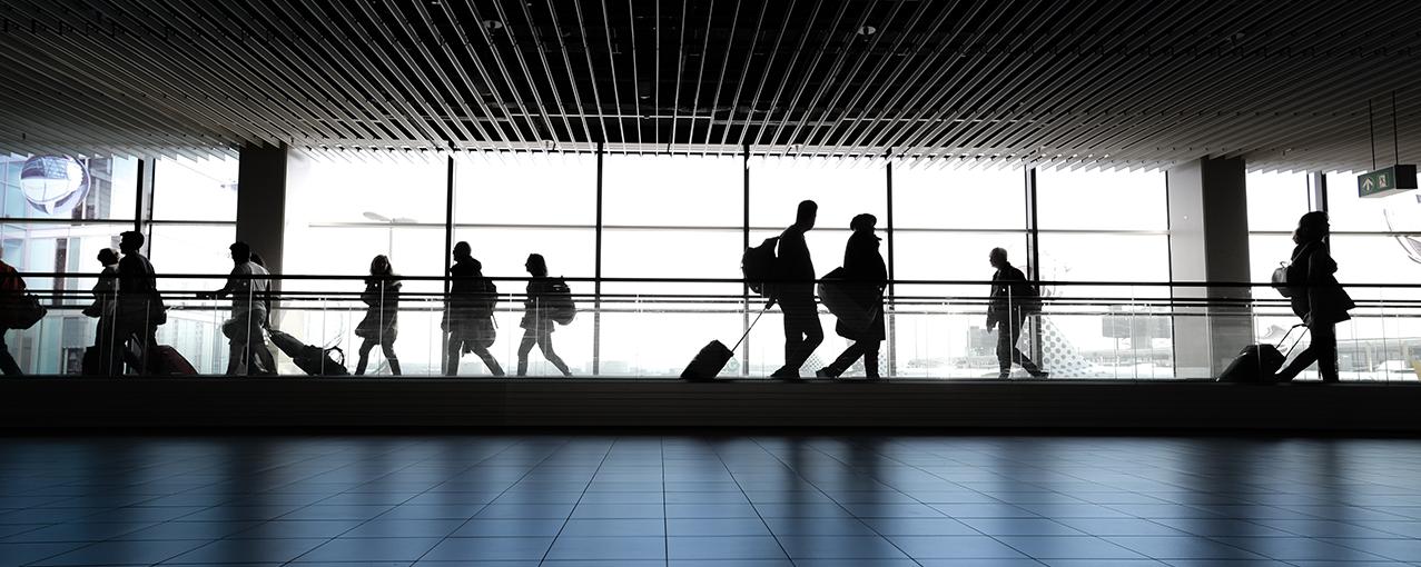 Em um aeroporto, pessoas caminham em direções diferentes carregando malas
