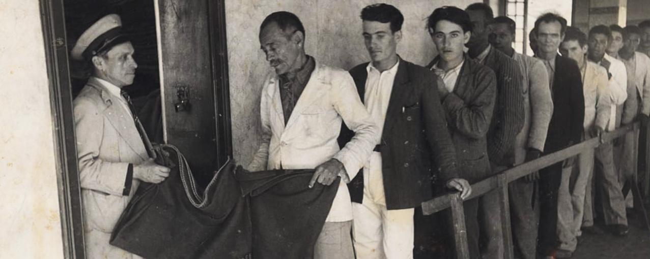 Em fila, um grupo formado por homens migrantes recebe cobertor de um funcionário da Hospedaria