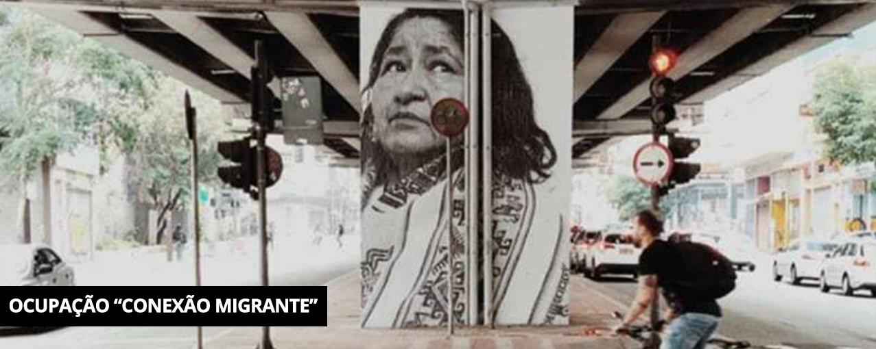 Fotografia retangular, colorida, mostrando a aplicação de uma fotografia da Diana Soliz, migrante boliviana, no Minhocão