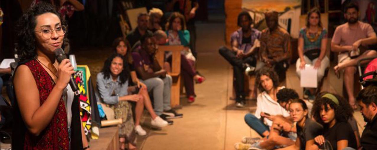 Em primeiro plano, do lado esquerdo, Rawa aparece com um microfone em mãos. No restante da foto, pessoas sentadas em bancos ou no chão prestam atenção