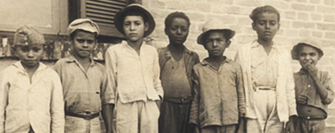 Imagem de acervo do Museu, na horizontal e em sépia, mostrando sete crianças nortistas