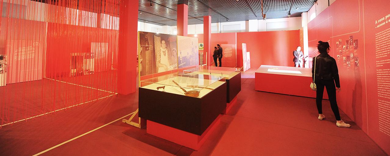 Uma sala vermelha conta com cortina à esquerda, vitrines no centro e uma mulher lendo informações na parede à direita