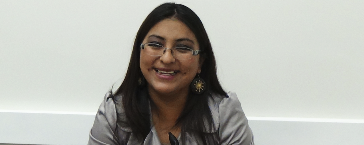 A fotografia mostra uma mulher, de origem boliviana, com cabelos escuros um pouco abaixo do ombro, blusa cinza e óculos. Ela está sorrindo