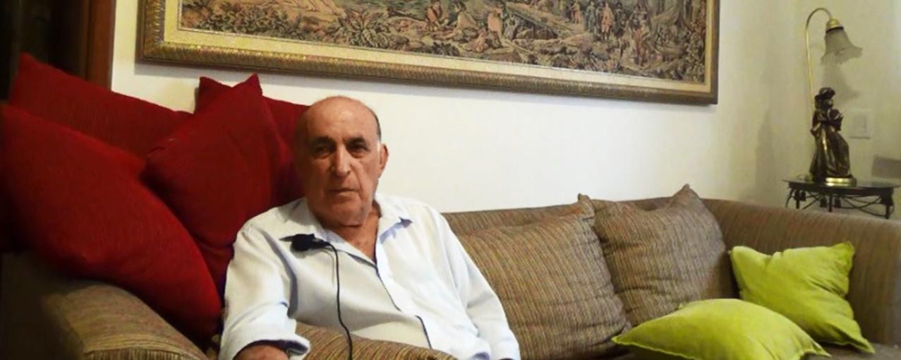 Na sala da sua casa, um homem está sentado em um sofá marrom claro, com almofadas vermelhas e verdes
