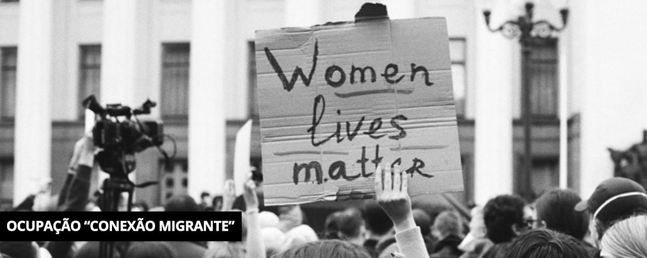Fotografia retangular, em preto e branco, mostrando um cartaz escrito 'Women lives matter' em uma manifestação
