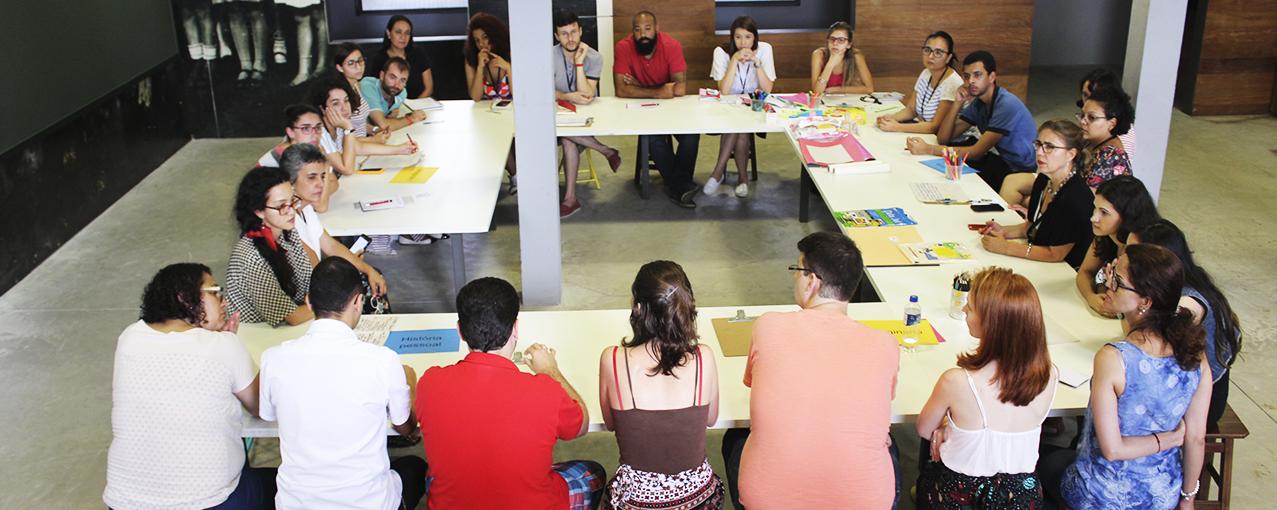 Em torno de uma mesa quadrada branca, homens e mulheres estão sentados conversando