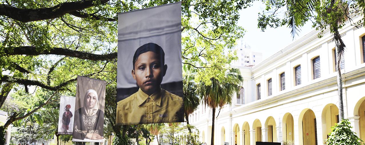 A imagem mostra fotos em grande escala dispostas no jardim do Museu da Imigração, penduradas nas árvores