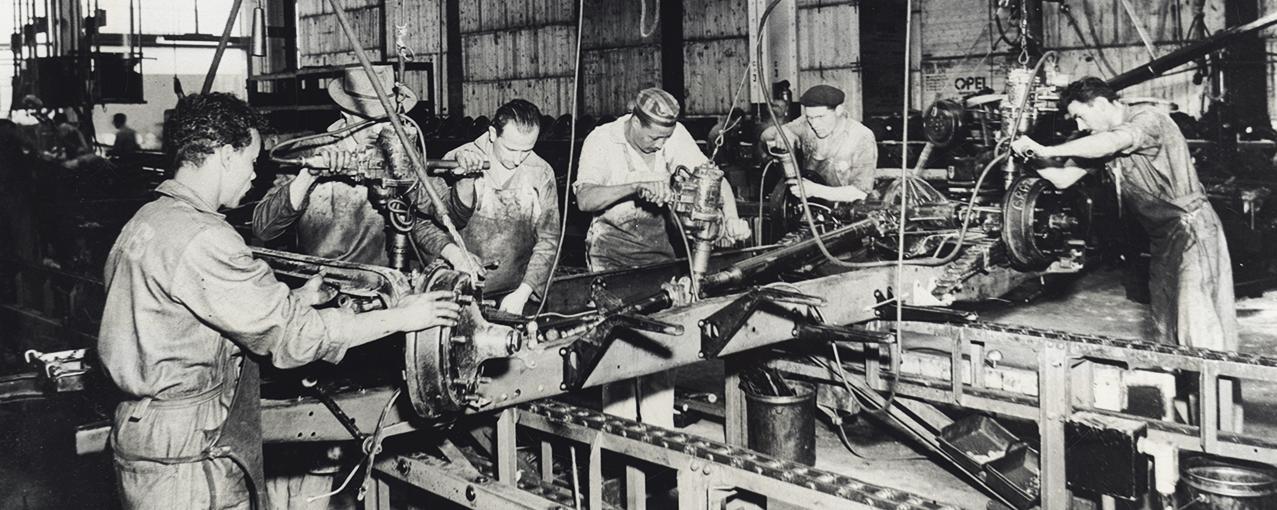 Em uma fábrica, seis homens operam maquinários em um dia de trabalho