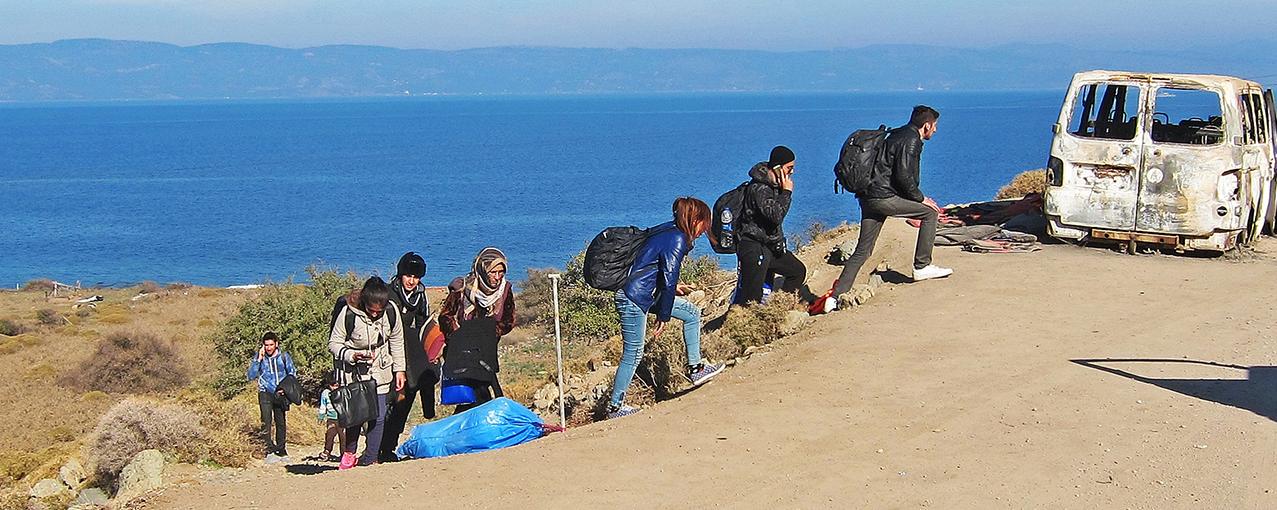 A imagem mostra oito pessoas subindo um morro em direção a uma estrada de terra. Aparecem, ainda, mar, céu e a carcaça de um carro