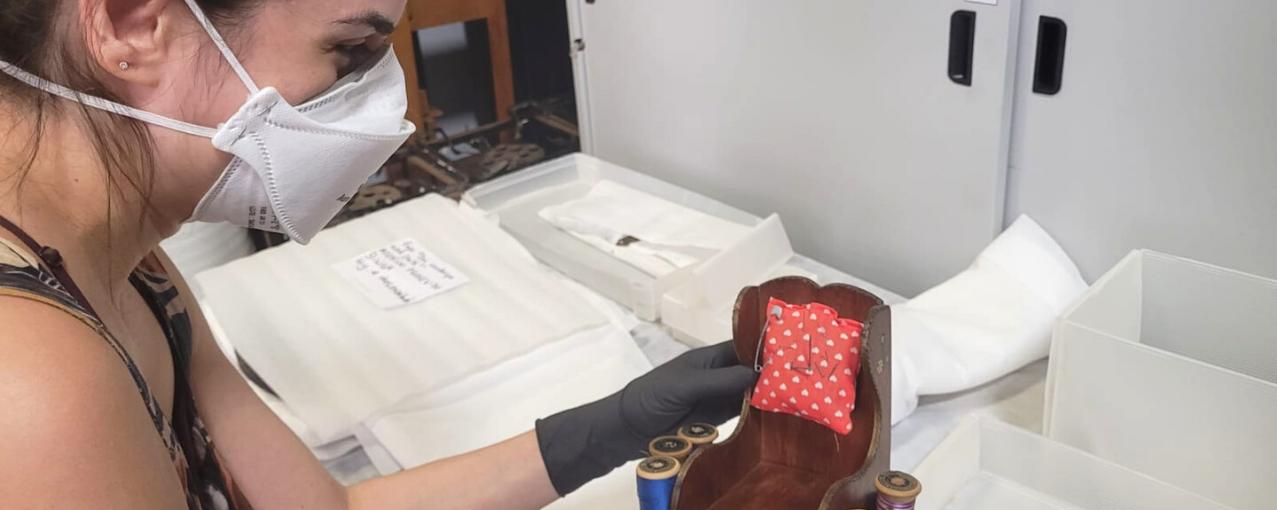 Na foto, a pesquisadora manuseia o objeto com luvas e máscara.