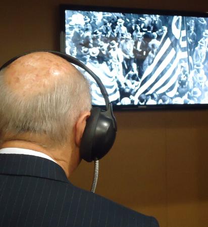 Foto de homem com fone em frente a uma tela de TV